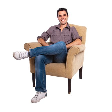 Portrait of a young man sitting on a sofa against a white background photo