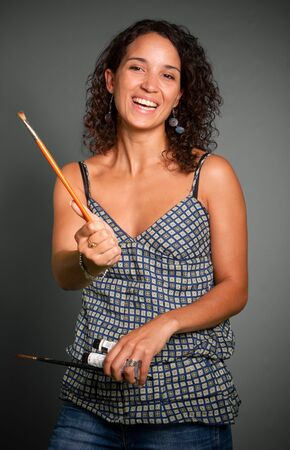 Young woman holding an canvas and some paint brushes Stock Photo - 5717354