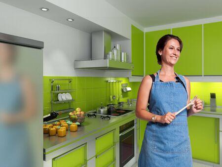 jasschort: lachende vrouw met een schort en een houten lepel in een moderne keuken
