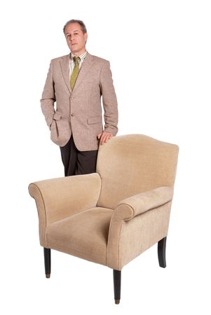 distinguished: Distinguished looking man leaning on an armchair Stock Photo