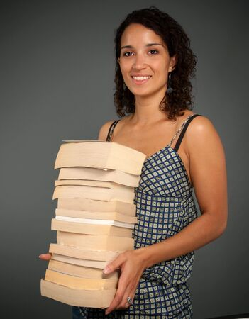 Young woman holding a pile of books Stock Photo - 5717359