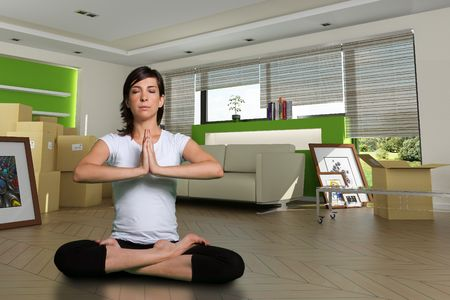 home made: Woman in lotus position in her new home. The images of the pictures are mine, and the label information is made up, so no copyright issue. Stock Photo