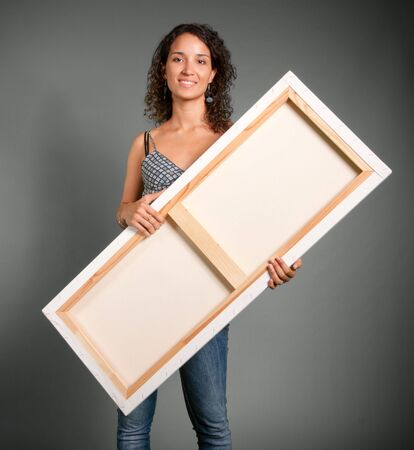 Young woman holding a canvas  Stock Photo - 5747192