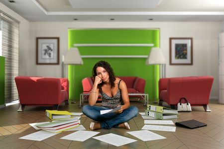 fedup: Fed-up woman at home surrounded by papers and files. The images on the pictures on the wall are mine, so no copyright issue.