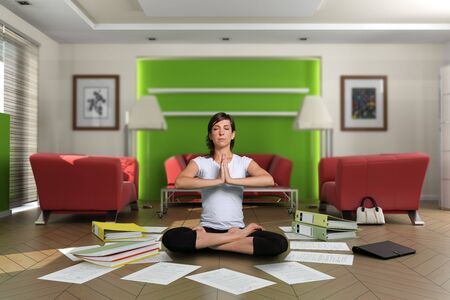 Woman in lotus pose in the middle of a chaotic living room with documents on the floor. The images on the pictures on the wall are mine, so no copyright issue.