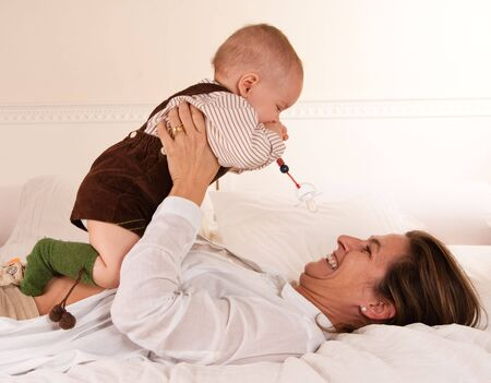 Woman lying on a bed playing with her baby boy Stock Photo - 6091349