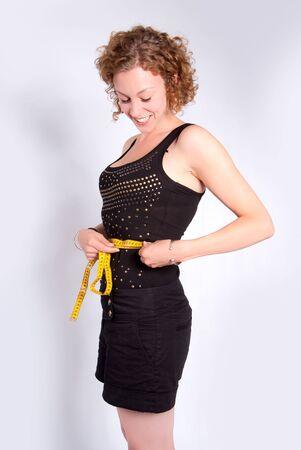 Ajustar joven medir sus residuos con una cinta métrica Foto de archivo