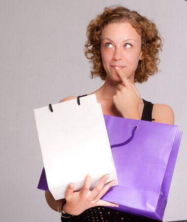 hesitating: Joven rubia vacila con dos bolsas de la compra