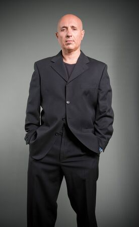 Serious looking bald man in a black costume photo