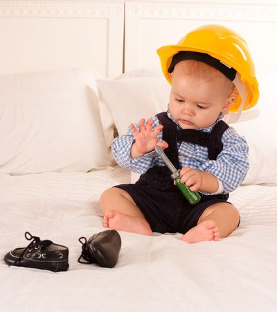 work wear:  Baby with a safety helmet and  a toy screwdriver  Stock Photo