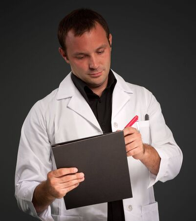 Young man with a medical uniform taking notes Stock Photo - 6368312