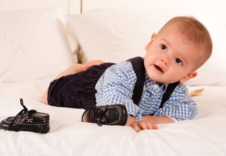 Cute baby boy crawling for his shoes on top of a bed  photo
