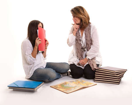 hushing:  Isolated image of a mother and a student daughter  with a hushing expression  Stock Photo