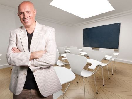 Mature teacher happily smiling in an empty classroom   photo