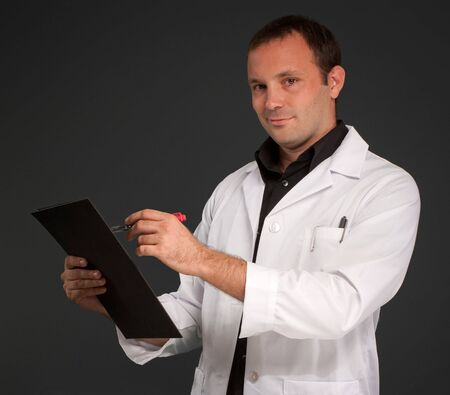 Cheerful man with a medical uniform taking notes Stock Photo - 6421883
