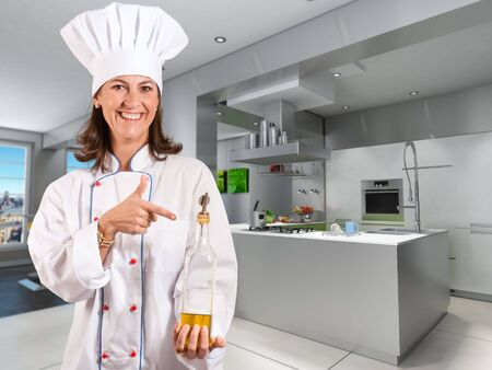 countertop:  Smiling female chef in a modern kitchen with a bottle of olive oil