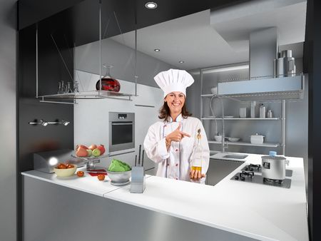 restaurant staff:   Smiling female chef behind a modern kitchen counter pointing at a bottle of olive oil