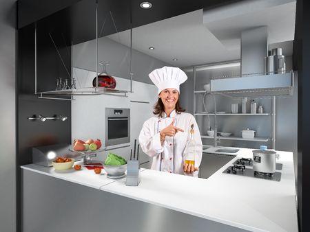 cocinas industriales: Sonriendo a cocinera detr�s de un mostrador de la cocina moderna apuntando a una botella de aceite de oliva