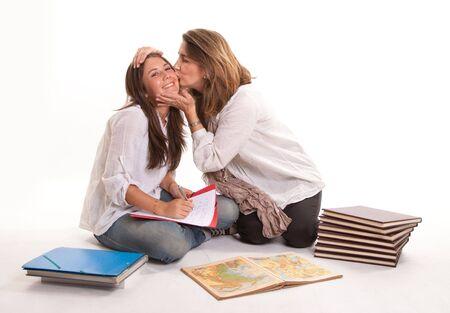 werkende moeder:  Geïsoleerde afbeelding van een moeder die haar tiener dochter kissing