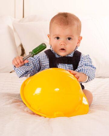 safety helmet:  Beb� con un casco de seguridad y un destornillador de juguete