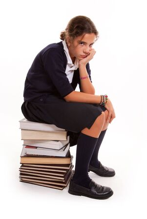 Schoolgirl with a bored look sitting on a pile of books photo