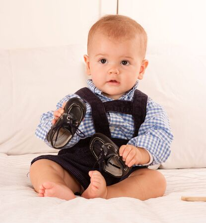 corduroy:  Cute baby boy in blue corduroy trousers playing with his shoes  Stock Photo