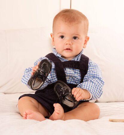 corduroy: Cute baby boy in pantaloni di velluto blu a giocare con le sue scarpe