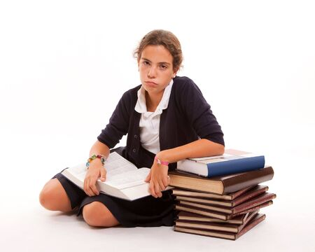 tiring: Schoolgirl with a bored look and a pile of books Stock Photo