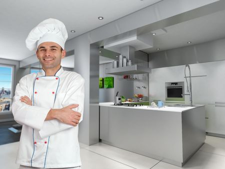 Smiling chef in a modern industrial metallic kitchen  photo