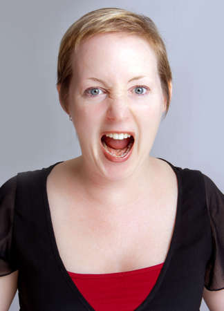 Angry  woman in a shouting fit against a neutral background Stock Photo - 6632015