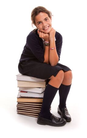 Happy looking student sitting on a pile of books photo