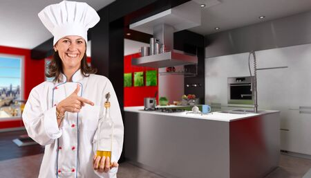 Smiling female chef in a modern kitchen with a bottle of olive oil  photo