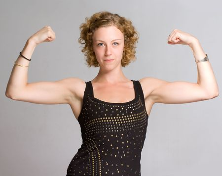 boasting:  Young blond woman showing her biceps