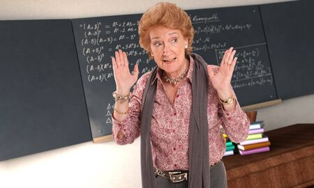 Maths teacher with an impatient gesture in and empty classroom   photo