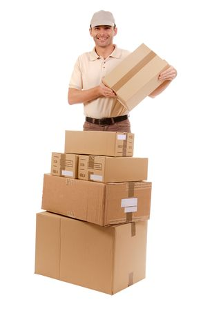 stockroom:  Isolated picture of a  cheerful messenger holding a cardboard box from a pile