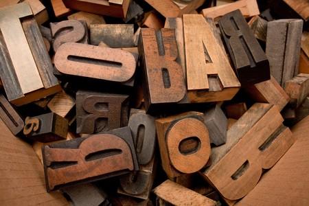 typescript:   Cardboard box with lots of wooden typescript letters