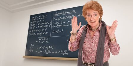 impatient:   Maths teacher with an impatient gesture with a blackboard as background   Stock Photo