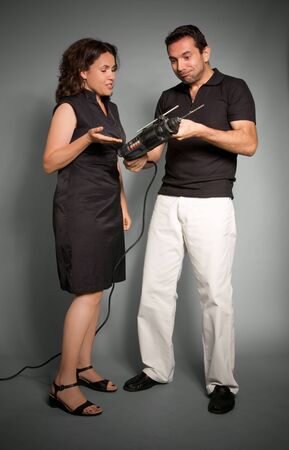 Couple looking perplexed to a hand drill  photo
