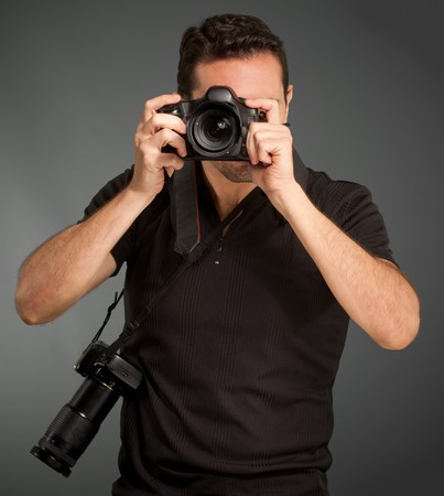 Man in black shooting with his camera with an extra one hanging from the strap  photo