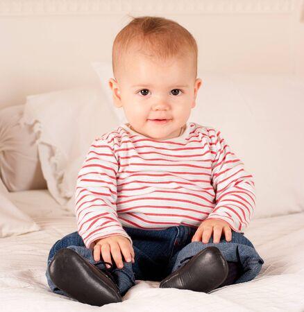 bebe sentado: Ni�o lindo en jeans y camiseta de rayas sentada en una cama