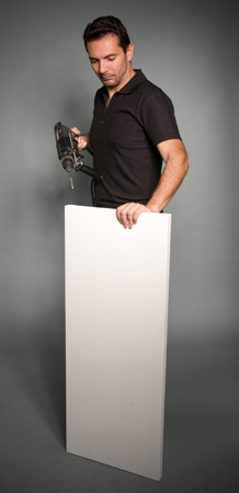 Man holding a hand drill and a whit board Stock Photo - 7051702
