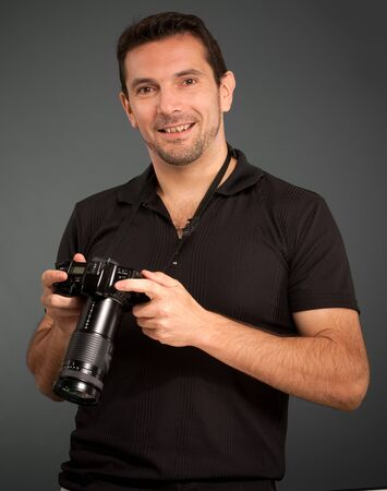 Man in black holding a photo camera  photo