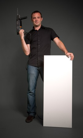 Man holding a drill and a vertical white board  photo