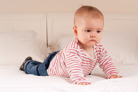 drool:  Cute baby boy on a bed trying to crawl