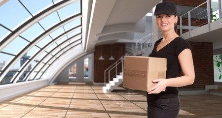 carrying box:  Female courier carrying a box in a huge loft