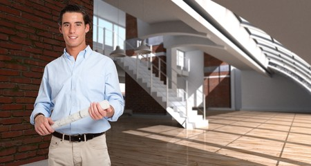 Young man holding a rolled-up plan in a empty loft Stock Photo - 7336539