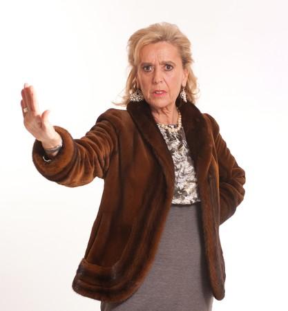 visone: Ritratto di signora senior inorridita elegante in un cappotto di visone con una mano di arresto