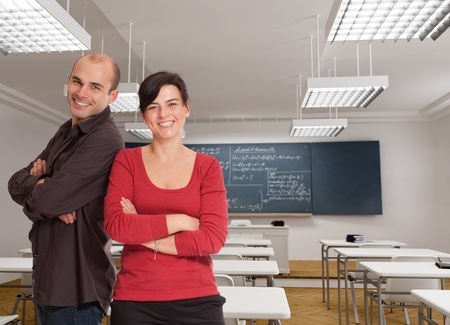 woman teacher:  A man and a woman cheerfully smiling on a classroom