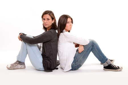 angry teenager:  Isolated picture of a serious mother back to back with her teenage daughter