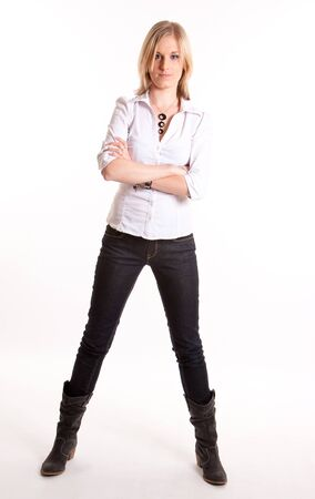 Young blond woman in jeans and boots standing against a white background